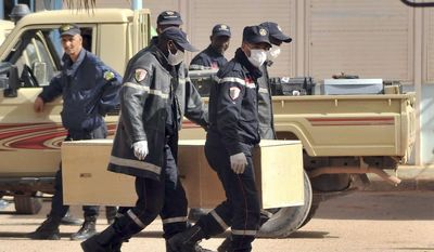 In this Jan. 21, 2013, file photo, Algerian firemen carry a coffin containing the body of a person killed during the gas facility hostage situation at the morgue in Ain Amenas, Algeria. The U.S. said the military launched an airstrike Saturday, June 13, 2015, targeting an al Qaeda leader in eastern Libya who has been charged with leading the attack on a gas plant in Algeria in 2013 that killed 35 hostages, including three Americans. The Libyan government and U.S. officials said warplanes targeted and likely killed Mokhtar BelMokhtar and several others. (AP Photo/Anis Belghoul, File)