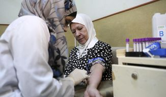In this Sunday, June 14, 2015, photo, a nurse takes blood from a patient at Jordan's National Center for Diabetes in Amman, Jordan. The center is particularly busy ahead of the Muslim holy month of Ramadan when diabetics seek advice on whether they can observe the sunrise-to-sundown Ramadan fast. (AP Photo/Khaled Al Odat)