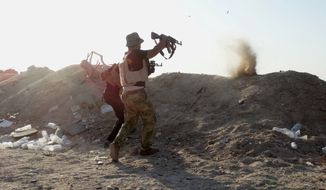 Iraqi security forces defend their positions against an Islamic State group attack in Husaybah, 8 kilometers (5 miles) east of Ramadi, Iraq, June 15, 2015. (Associated Press) ** FILE **