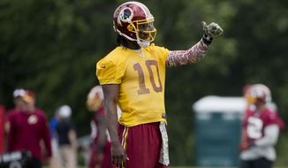 Washington Redskins quarterback Robert Griffin III gestures as he takes part in drills during an NFL football minicamp at Redskins Park Tuesday, June 16, 2015 in Ashburn, Va. (AP Photo/Pablo Martinez Monsivais)