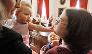 Kim O'Leary, right, holds her son D.J., as Emily Tringe, left, reaches from the arms of her mother, Heidi, during a bill-signing by Gov. Jim Douglas, rear, seated, in Montpelier, Vt., Thursday, May 15, 2008.  The governor signed a bill that will make it easier for nursing mothers to continue breast-feeding their babies after they return to work. The bill requires employers to allow employees to express milk for their child while at work and to provide a private space to do so. (AP Photo/Toby Talbot)