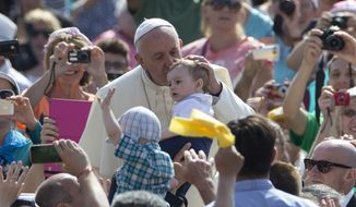 Pope Francis kisses a baby as he arrives for his weekly general audience, in St. Peter's Square at the Vatican,  Wednesday, June 17, 2015. (AP Photo/Andrew Medichini)