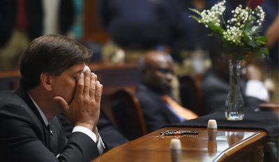 State Sen. Vincent Sheheen gets emtional as he sits next to the draped desk of state Sen. Clementa Pinckney, Thursday at the Statehouse in Columbia, South Carolina. (Associated Press photographs)