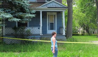 A woman walks by a vacant Niagara Falls, N.Y., house, Thursday, June 18, 2015, two days after the dismembered body of murder victim Terri Lynn Bills was found inside. Another woman was similarly dismembered in Niagara Falls in 2012.  That case remains unsolved. (AP Photo/Carolyn Thompson)