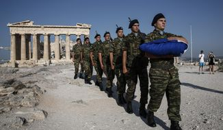 An army contingent carry a Greek flag in front of the temple of the Parthenon before a hoisting ceremony at the Acropolis hill in Athens, Greece Thursday, June 18, 2015. Greece and its creditors publicly blamed one another for an impasse in bailout talks, on the eve of a eurozone finance ministers' meeting billed as key to their outcome. (AP Photo/Yorgos Karahalis)