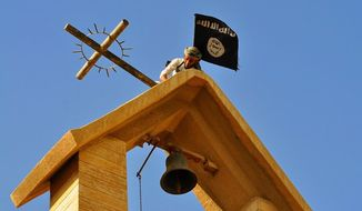 In this photo released on March 7, 2015 by a militant website, which has been verified and is consistent with other AP reporting, a member of the Islamic State group holds the IS flag as he dismantles a cross on the top of a church in Mosul, Iraq. (Militant website via AP)