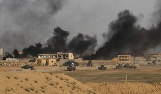 FILE - In this Friday, March 27, 2015 file photo, Iraqi security forces prepare to attack Islamic State extremist positions as smoke rises from central Tikrit, Iraq during clashes in the city, 130 kilometers (80 miles) north of Baghdad. (AP Photo/Khalid Mohammed)