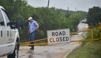 Denton County Road & Bridge crews from Precinct 1 close Rector Road north of FM 156 between Krum and Sanger because of high water from Tropical Storm Bill Wednesday, June 17, 2015, in Denton, Texas.  (Al Key/The Denton Record-Chronicle via AP)