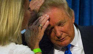 Republican presidential candidate Donald Trump asks N.H. House Rep. Claire Rouillard, left, to confirm that his hair is real during a rally at Manchester Community College in Manchester, N.H., on Wednesday, June 17, 2015. Trump announced his candidacy for President  yesterday. (Elizabeth Frantz/Concord Monitor via AP)