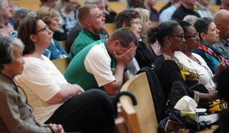 A man holds his head during a memorial service for six Irish students at the Cathedral of Christ the Light Wednesday, June 17, 2015, in Oakland, Calif. The six Irish students died when a balcony collapsed during a party in Berkeley.  (AP Photo/Beck Diefenbach)