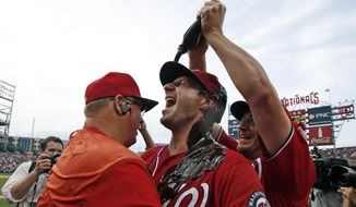 Washington Nationals' Jordan Zimmermann, right, douses starting pitcher Max Scherzer with chocolate syrup as Scherzer hugs pitching coach Steve McCatty, left, after Scherzer's no-hitter baseball game against the Pittsburgh Pirates at Nationals Park, Saturday, June 20, 2015, in Washington. The Nationals won 6-0. (AP Photo/Alex Brandon)
