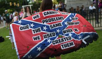 Mariangeles Borghini holds a burned Confederate flag during a rally to take down the Confederate flag at the South Carolina Statehouse, Saturday, June 20, 2015, in Columbia, S.C. Rep. Doug Brannon, R-Landrum, said it's past time for the Confederate flag to be removed from South Carolina's Statehouse grounds after nine people were killed at the Emanuel AME Church shooting. (AP Photo/Rainier Ehrhardt)