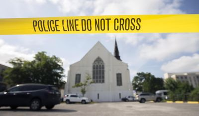 Police tape surrounds the parking lot behind the AME Emanuel Church as FBI forensic experts work the crime scene, Friday, June 19, 2015 where nine people where shot by Dylann Storm Roof, 21, on Wednesday in Charleston, S.C. The current brick Gothic revival edifice, completed in 1891 to replace an earlier building heavily damaged in an earthquake, was a mandatory stop for the likes of Booker T. Washington and the Rev. Martin Luther King Jr. Still, Emanuel was not just a church for the black community. (AP Photo/Stephen B. Morton, File)