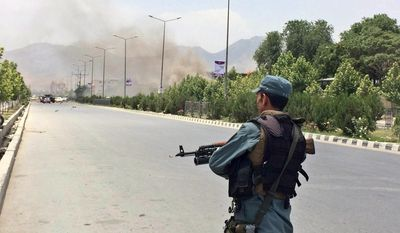 An Afghan security officer stands guard at the entry gate of the Afghan parliament after an attack by the Taliban, in Kabul, Afghanistan, Monday, June 22, 2015. (AP Photo/Rahmat Gul)