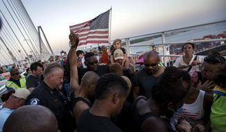 People raise their hands as a show of unity as thousands of marchers meet in the middle of Charleston's main bridge after nine black church parishioners were gunned down during a Bible study, Sunday, June 21, 2015, in Charleston, S.C. (AP Photo/Stephen B. Morton)