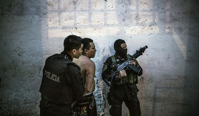 In this May 28, 2015 photo, members of the fast response police units, known as Halcones, detain a suspected gang member, who was found out of breath on abed followinga chase by police, in San Salvador, El Salvador. Observers blame the worsening insecurity on the breakdown of a 1.5-year-old truce between the gangs and the government. While the homicide rate plunged, critics say the truce gave the gangs time to strengthen, train and acquire heavier arms than they had in the past. (AP Photo/Manu Brabo)