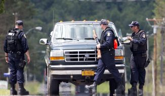 Corrections officers stop a vehicle as the search for two escaped prisoners from Clinton Correctional Facility in Dannemora continues Monday, June 22, 2015, in Owls Head, N.Y. Searchers on Monday swarmed the heavily wooded area about 20 miles west of the maximum-security Clinton Correctional Facility. (AP Photo/Mike Groll)