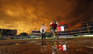 A member of the grounds crew works on the field as the sunset turns the sky a golden yellow during a rain delay before a baseball game between the Washington Nationals and the Atlanta Braves at Nationals Park, Tuesday, June 23, 2015, in Washington. (AP Photo/Alex Brandon)