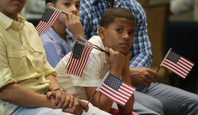 Derek Martinez listens during a ceremony to receive a citizenship certificate at the Bronx Zoo, Tuesday, May 26, 2015, in New York. Twenty five children, whose immigrant parents were naturalized recently, participated in a ceremony to receive the certificates from the U.S. Citizenship and Immigration Services.(AP Photo/Julie Jacobson)