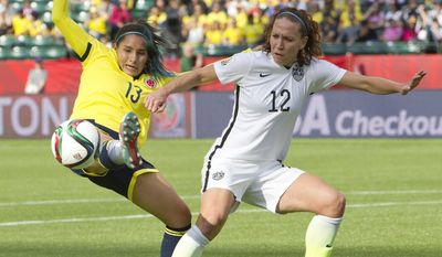 Colombia's Angela Clavijo (13) stretches for the ball in front of United States' Lauren Holiday  during first half FIFA Women's World Cup round of 16 soccer action in Edmonton, Alberta, Canada, Monday, June 22, 2015.  (Jason Franson/The Canadian Press via AP) MANDATORY CREDIT