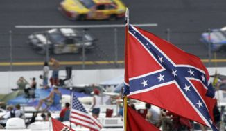 FILE - In this Oct. 7, 2007, file photo, a Confederate flags fly in the infield as cars come out of turn one during a NASCAR auto race at Talladega Superspeedway in Talladega, Ala. NASCAR is backing South Carolina Gov. Nikki Haley's call to remove the Confederate flag from the South Carolina Statehouse grounds in the wake of a massacre at a Charleston church, it said in a statement Tuesday, June 23, 2015. Though NASCAR bars the use of the flag in any official capacity, many fans fly the flag at their races.  (AP Photo/Rob Carr, File)