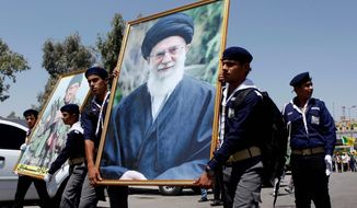 Iraqi Hezbollah scouts parade with a portrait of Iranian Supreme Leader Ayatollah Ali Khamenei as they mark Al-Quds Day in Baghdad. Tehran's mullahs have armed Lebanese militant groups and backed Syria's Bashar Assad against the Islamic State. (Associated Press) ** FILE **