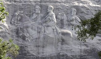 This photo shows a carving depicting confederates Stonewall Jackson, Robert E. Lee and Jefferson Davis, Tuesday, June 23, 2015, in Stone Mountain, Ga. Calls to remove Confederate imagery from public places multiplied rapidly across the South and beyond Tuesday with opponents eyeing state flags, license plates and statues of Civil War politicians and generals. (AP Photo/John Bazemore)