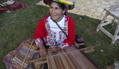 Peru program participant Quintina Huanca weaves fabric at the Smithsonian Folklife Festival in Washington, Wednesday, June 24, 2015. Peru's artists, cultures and famous foods are being featured in the Smithsonian Folklife Festival this year on the National Mall as the South American nation aims to boost tourism and cultural exchange. The festival reopens Wednesday, July, 1 and runs thru July 5. (AP Photo/Molly Riley)