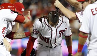 CORRECTS THAT DESMOND HIT SACRIFICE FLY, INSTEAD OF SINGLE - Washington Nationals' Ian Desmond is doused with chocolate syrup by Max Scherzer, right, after a baseball game against the Atlanta Braves at Nationals Park, Wednesday, June 24, 2015, in Washington. Desmond hit a sacrifice fly to score the winning run. The Nationals won 2-1 in 11 innings. (AP Photo/Alex Brandon)