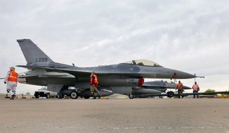 In this May 15, 2015, file photo, a boneyard crew tows an F-16 Fighting Falcon aircraft prior to the preservation process after its arrival at the 309th Aerospace Maintenance and Regeneration Group at Davis-Monthan Air Force Base in Tucson, Ariz. (AP Photo/Matt York, File)