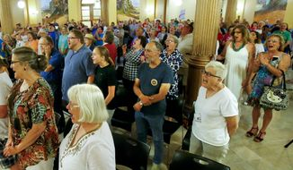 """Supporters of the LGBT community yell the word """"freedom"""" during a rally on Friday, June 26, 2015, at the Kansas Statehouse in Topeka, Kan. The Supreme Court's decision extends the right to marry to same-sex couples nationwide. (Chris Neal/The Topeka Capital-Journal via Associated Press)"""