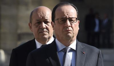 French President Francois Hollande and Defence Minister Jean-Yves Le Drian, behind, review troops during a military ceremony at the Hotel des Invalides in Paris, France, Thursday, June 25, 2015. (Dominique Faget, Pool via AP)