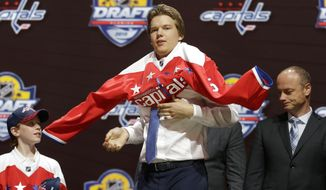Ilya Samsonov, center, of Russia, puts on a Washington Capitals sweater after being chosen 22nd overall during the first round of the NHL hockey draft, Friday, June 26, 2015, in Sunrise, Fla. (AP Photo/Alan Diaz)