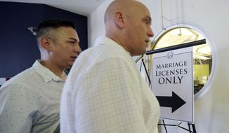 A couple arrives at the Travis County building to apply for a marriage license at after the US. Supreme Court ruled that  same-sex couples have the right to marry nationwide, Friday, June 26, 2015, in Austin, Texas. The court's 5-4 ruling means the remaining 14 states, in the South and Midwest, will have to stop enforcing their bans on same-sex marriage. (AP Photo/Eric Gay)