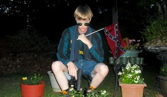This undated file image that appeared on Lastrhodesian.com, a website being investigated by the FBI in connection with Charleston, S.C., shooting suspect Dylann Roof, shows Roof posing for a photo while holding a Confederate flag. Roof is accused of killing nine people inside Emanuel African Methodist Episcopal Church in Charleston. (Lastrhodesian.com via AP, File)