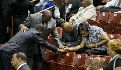 Mourners pray before the funeral service for Sen. Clementa Pinckney, Friday, June 26, 2015, in Charleston, S.C. President Barack Obama will deliver the eulogy at Pinckney's funeral Friday at College of Charleston's TD Arena  near the Emanuel AME Church, the scene of last week's shooting. (AP Photo/David Goldman)