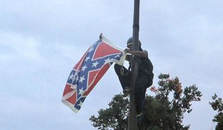Bree Newsome of Charlotte, N.C., removes the Confederate battle flag at a Confederate monument at the Statehouse in Columbia, S.C., on Saturday, June, 27, 2015. She was taken into custody when she came down. The flag was raised again by Capitol workers about 45 minutes later.  (AP Photo/Bruce Smith) ** FILE **