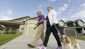 Amy Shives, right, and her husband George walk their cavalier King Charles spaniel Chester in their neighborhood, Wednesday, June 3, 2015, in Spokane, Wash. Amy Shives was diagnosed with early onset Alzheimer's disease in 2011 and has since been involved with the Alzheimer's Association. Nearly two-thirds of Americans with Alzheimer's disease are women, and now some scientists are questioning the long-held assumption that it's just because women tend to live longer than men. (AP Photo/Young Kwak)