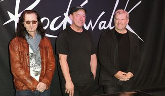 Rush guitarist Alex Lifeson (right), bassist/vocalist Geddy Lee (left) and drummer Neil Peart. (Invision via Associated Press)