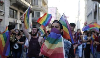 Participants of a Gay Pride event in support of  Lesbian, Gay, Bisexual and Transsexual (LGBT) rights chant slogans after police sprayed water canon to disperse them, in Istanbul, Sunday, June 28, 2015. Turkish police have used water cannons and tear gas to clear gay pride demonstrators from Istanbul's central square. It wasn't immediately clear why the police intervened to push the peaceful if noisy protest away from the area. Demonstrators regrouped a few blocks down the street and continued to dance and chant slogans against homophobia without any further clashes. (AP Photo/Emrah Gurel)