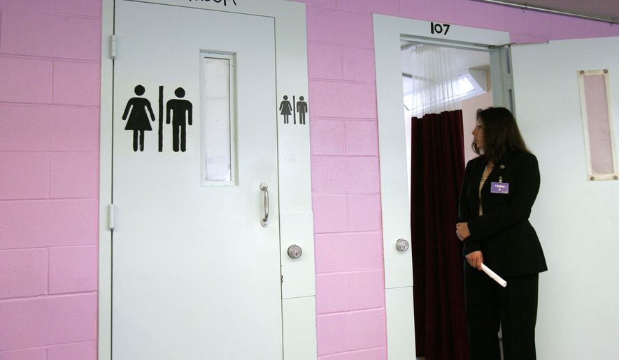 Immigration Agent Cynthia Guerra looks into a sleeping area at the T. Don Hutto Residential Center in Taylor, Texas. Shown at left is one of two private restrooms added to this dorm area. (Associated Press)