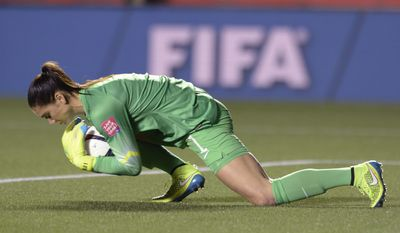 U.S. keeper Hope Solo covers the ball after making a save against China during the second half of a quarterfinal match in the FIFA Women's World Cup soccer tournament, Friday, June 26, 2015, in Ottawa, Ontario, Canada. (Adrian Wyld/The Canadian Press via AP)