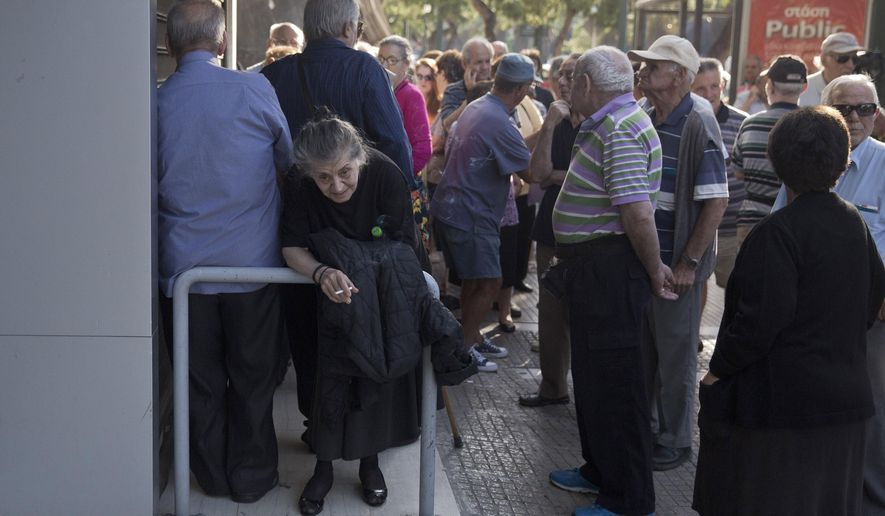 Elderly people, who usually get their pensions at the end of the month, wait outside a closed bank in Athens, Monday, June 29, 2015. Greece's five-year financial crisis took its most dramatic turn yet, with the cabinet deciding that Greek banks would remain shut for six business days and restrictions would be imposed on cash withdrawals. (AP Photo/Petros Giannakouris)