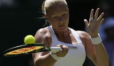 Kiki Bertens of the Netherlands returns a ball to Petra Kvitova of the Czech Republic during the singles first round match at the All England Lawn Tennis Championships in Wimbledon, London, Tuesday June 30, 2015. (AP Photo/Tim Ireland)