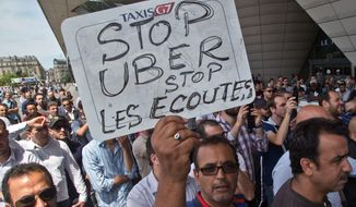 """French taxi drivers protested, and authorities took two Uber managers into custody for questioning last week over """"illicit activity"""" involving the low-cost ride-hailing service. (Associated Press)"""