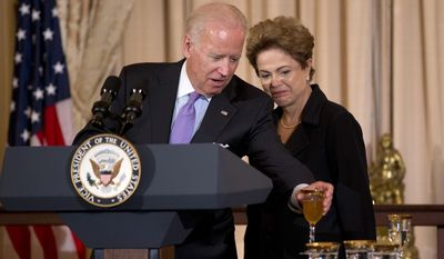 Brazilian President Dilma Rousseff watches as Vice President Joe Biden puts his glass on a table after a toast during a luncheon in her honor, Tuesday, June 30, 2015, at the State Department in Washington.    (AP Photo/Manuel Balce Ceneta)