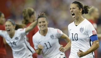 Carli Lloyd (10) of the U.S. Women's National Soccer Team celebrates with teammates Ali Krieger (11) and Morgan Brian after scoring on a penalty kick against Germany during the second half of Tuesday's World Cup semifinal in Montreal, Canada. (Associated Press)