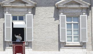 Pope Francis blesses the faithful as he celebrates the Angelus noon prayer from the window of his studio overlooking St. Peter's Square at the Vatican, Monday, June 29, 2015. (AP Photo/Gregorio Borgia)