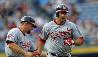 Washington Nationals first baseman Clint Robinson (25) is congratulated by third base coach Bob Henley (14) as he rounds third base after hitting a two-run home run in the first inning of a baseball game against the Atlanta Braves Tuesday, June 30, 2015, in Atlanta.  (AP Photo/John Bazemore)