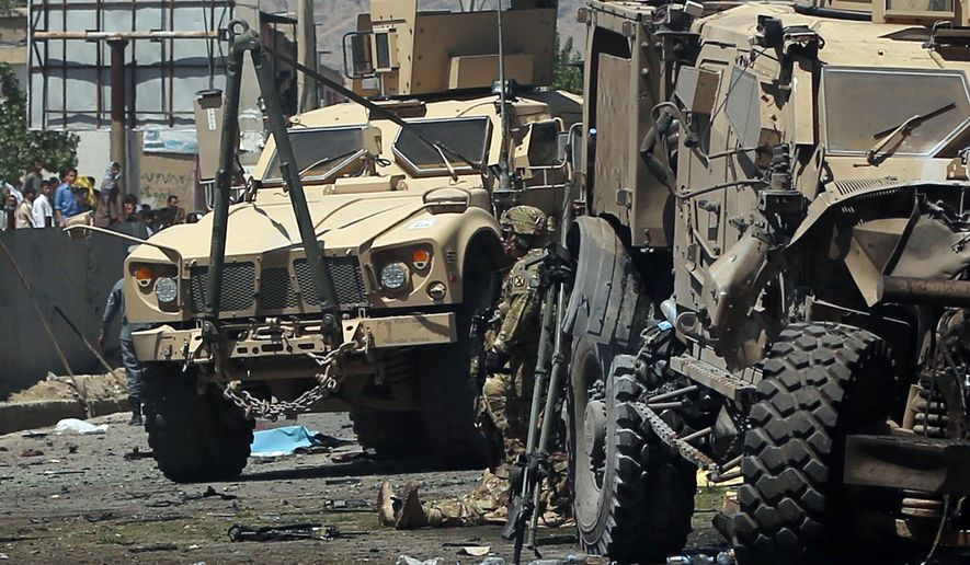 Armored vehicles remain at the site of a blast targeting the NATO convoy in Kabul, Afghanistan, Tuesday, June 30, 2015. It comes a week after an audacious attack on the nation's parliament, which highlighted the ability of insurgents, who have been fighting to overthrow the Kabul government for almost 14 years, to enter the highly fortified capital to stage deadly attacks. (AP Photo/Massoud Hossasini)